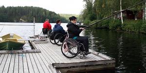 Pyörätuolilaisia kalastamassa laiturilla