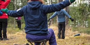 Ihmisiä metsässä tekemässä hengitysharjoitusta.
