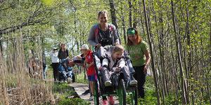 Iloinen perhe metsässä pitkospuilla. Edessä lapsi pyörätuolissa, rinnalla pari muuta lasta.
